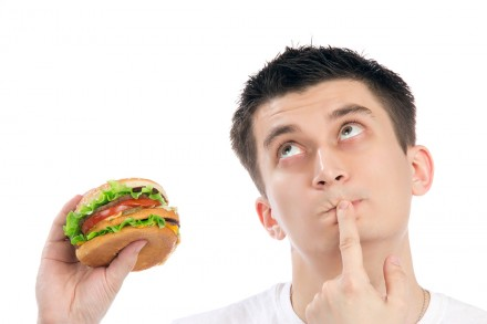 Young man with tasty fast food unhealthy burger