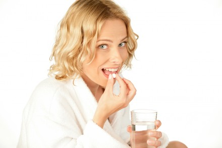 Portrait of young smiling woman with pill